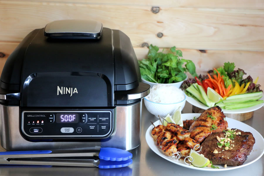 The Ninja Foodi Grill on a counter next to a Vietnemese Mixed Grill Platter