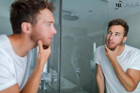 Man checking his face in the mirror - ML Delicate Beauty