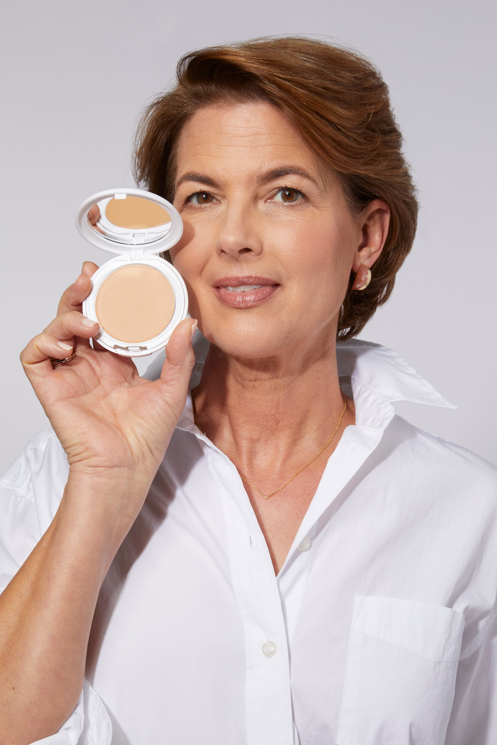 Model in a white shirt holding up a pressed powder compact