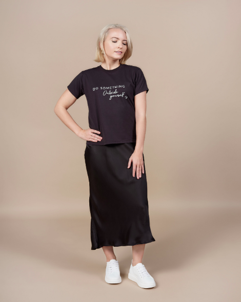 """A blonde woman wearing a black satin maxi skirt and a black T-shirt that reads """"do something outside yourself"""""""
