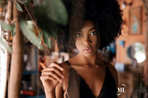 A black skin woman holding a branch - Delicate Beauty
